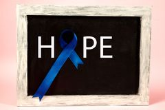 Colon cancer awareness poster. Blue ribbon made of dots on white background. Medical concept. royalty free stock photos