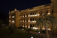 Colonade in the night. Beautiful villa in ancient greek classic style with landscaped green territory; outdoor panorama with copy space Royalty Free Stock Images