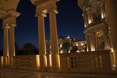 Colonade in the night. Beautiful villa in ancient greek classic style with landscaped green territory; outdoor panorama with copy space royalty free stock photo