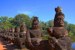 Colonade of stone statues as a railing on the bridge. In front of Angor wat temple in Cambodia Stock Photography