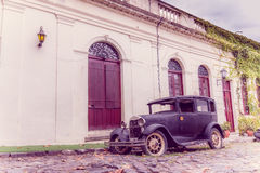 COLONIA DEL SACRAMENTO, URUGUAY - MAY 04, 2016: rustic old car parked in the street next to an ancient house Royalty Free Stock Photos