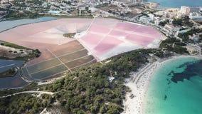 Colonia Sant Jordi, Espanha de Mallorca Paisagem aérea do zangão da vila, dos planos cor-de-rosa de sal e da praia encantador Est video estoque