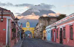 Colonial Spanish Architecture Santa Catalina Arch Agua Volcano Antigua Guatemala. Colonial Architecture and Street Scene during Early Morning Sunrise in Antigua royalty free stock photo