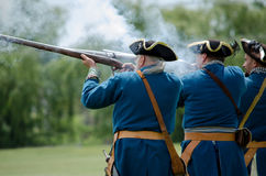 Colonial blue soldiers fire weapons Stock Photos