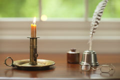 Colonial candle, quill pen and glasses on desk with window. An colonial candle holder with a quill pen and glasses in front of a window stock photo