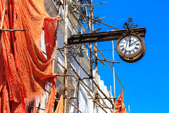 Colonial clock hanging on an old colonial building Stock Photos