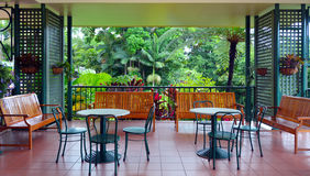 Colonial furnitures on a balcony against a tropical rain forest Royalty Free Stock Image