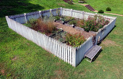 Colonial Garden with Raised Vegetable Plant Beds. Antique colonial garden with old fashioned white picket fence and raised plant beds for vegetable and spice Stock Photos
