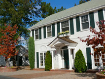 Colonial House. Currently a private school, white wooden walls, large windows and an impressing entrance. Brick driveway and green windows and bushes. Trees in Stock Photo