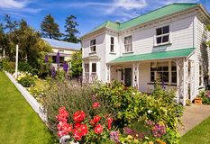 Colonial house in Akaroa. Colonial house with beatiful flowers in Akaroa, South Island, New Zealand Stock Images