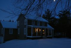 Free Colonial House At Night With Snow Covered Ground And Moon Shinning Above Tree Limbs Stock Photo - 137140160