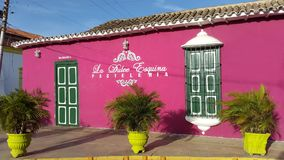 Colonial house in Paraguana peninsule, Pueblo Nuevo, Falcon state Venezuela. Front view for colonial house green and fucsia converted in bakery in Pueblo Nuevo stock photo