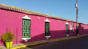 Colonial house in Paraguana peninsule, Pueblo Nuevo, falcon state Venezuela. Front view for colonial house green and fucsia converted in bakery in Pueblo Nuevo stock image