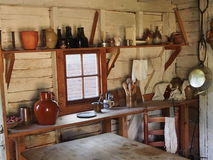 Colonial Kitchen. Shelves of bottles, pans, and utensils line the shelves of a colonial kitchen on a middling plantation Stock Image