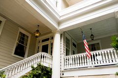 American flag outside white wooden american home porch in charleston south carolina. Colonial style house with porch and american flag Royalty Free Stock Image