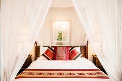Colonial style wooden four poster bed with curtain, colourful pi. Mar 11, 2014 BANGKOK, Thailand  : Vintage Colonial style wooden four poster bed with curtain Stock Photos