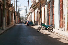 Colonial town cityscape of Trinidad, Cuba. Old fashioned motocycle. Royalty Free Stock Photos