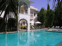 Colonial villa with pool. In India with green garden and palms royalty free stock photography