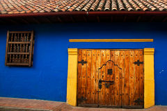 Colonial Wall and Door. Blue wall in the Spanish colonial style in the neighborhood La Candelaria in Bogota, Colombia Stock Photo