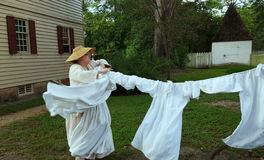 Colonial Williamsburg reenactor taking down dried laundry. Colonial woman rushes to take in the laundry before rain Stock Photography