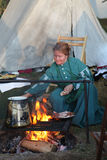 Colonial woman cooking over a fire. Woman in Colonial cooking over a hot  fire  at the reenactment of the Battle of Pilot Knob in Ironton, Missouri's  Fort Stock Image
