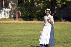 Colonial Woman with a Mug. A colonial actor walks through a field carrying a mug Royalty Free Stock Photography