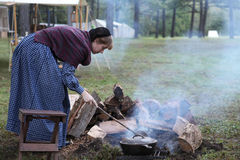 Colonial woman tends fire. Woman in Colonial attire tends a fire for cooking  at the reenactment of the Battle of Pilot Knob in Ironton, Missouri's  Fort Stock Photo