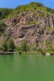 Colonna di acqua verde alla riva con un'alta scogliera rocciosa Alla cima della scogliera è un'erba verde smeraldo Immagine Stock