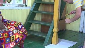 Colonna di legno della pittura dell'uomo del lavoratore con la spazzola nella propria aula magna 4K video d archivio