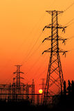 Colonna elettrica ad alta tensione sul fondo di tramonto Immagine Stock