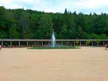 Colonnade of Luhacovice spa, fountain, people, trees and forest in the background royalty free stock image