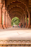Colonnade, Red Fort, Delhi. Delhi, India - 2014, December 26 : Some people in a colonnade of red sandstone decorated columns inside the Red Fort of Old Delhi Royalty Free Stock Photo