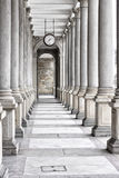 Colonnade of tall columns with clock by the ceiling Stock Images