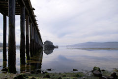 Colonnade wooden pillars in water leaving pier on Gulf Pacific_ Stock Photos
