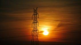 Colonne électrique à haute tension de lignes électriques pendant le coucher du soleil Images libres de droits