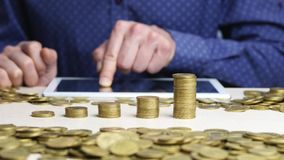 Colonne in aumento delle monete Lavoro dell'uomo sulla compressa digitale video d archivio