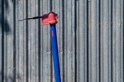 Colonne d'eau de rue contre un plat industriel de zinc Photographie stock libre de droits