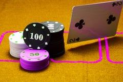 Colonne dei chip di poker che cadono sulle carte da gioco di una tavola fotografie stock