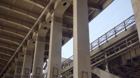 Colonne del metallo del ponte e del treno che passano nel fondo video d archivio
