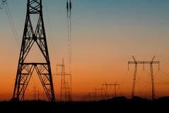 Colonne delle linee ad alta tensione al tramonto Fotografie Stock