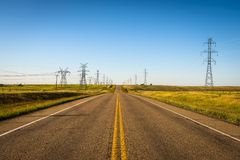 Colonne di elettricità lungo una strada vuota in Alberta, Canada Fotografia Stock