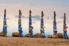 Colonne rituali di legno con i nastri variopinti Hadak su capo Burkhan Lago Baikal Isola di Olkhon La Russia Immagine Stock