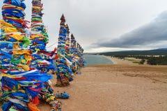 Colonne rituali di legno con i nastri variopinti Hadak su capo Burkhan Lago Baikal Isola di Olkhon La Russia Fotografia Stock