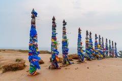 Colonne rituali di legno con i nastri variopinti Hadak su capo Burkhan Lago Baikal Isola di Olkhon La Russia Immagine Stock Libera da Diritti