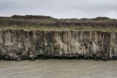 Colonne scure del basalto e un funzionamento sotto loro, Islanda del fiume Fotografia Stock Libera da Diritti