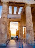 Colonnes de passage d'entrée de Propylaea d'Acropole, Athènes, Grèce donnant sur le coucher du soleil et la ville photographie stock libre de droits