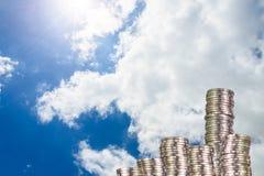 Colonnes des pièces de monnaie, piles des pièces de monnaie disposées comme graphique sur le ciel bleu Image libre de droits
