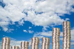 Colonnes des pièces de monnaie, piles des pièces de monnaie disposées comme graphique sur le ciel bleu Images stock