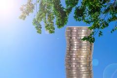 Colonnes des pièces de monnaie, piles des pièces de monnaie disposées comme graphique sur le ciel bleu Photos stock
