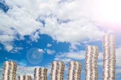 Colonnes des pièces de monnaie, piles des pièces de monnaie disposées comme graphique sur le ciel bleu Photographie stock